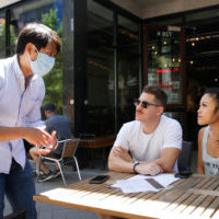 Cheng Wang, co-owner of the MidiCi Neapolitan Pizza restaurant, left, discusses the menu with diners, Ethan Rippy, center, and Ellie Vu in Sacramento, Calif., Friday, May 22, 2020. As part of Sacramento County's extended Stage 2 reopening plan, dine-in restaurants and retail stores were allowed to open noon Friday after being closed for months due to the coronavirus pandemic. (AP Photo/Rich Pedroncelli)