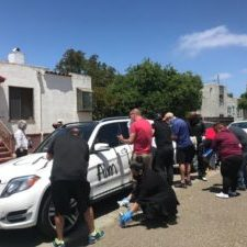 """Neighbors help clean """"All Lives Matter"""" graffiti off of the car of a Black Alameda resident after it was vandalized the night before. (Rachel Wellman/Instagram)"""